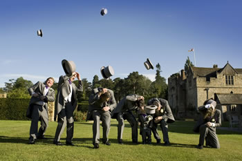 Groom and Ushers throwing their hats into the air at Hever Castle. Photograph by Kenny Hickey