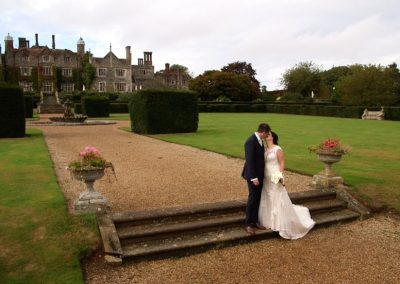 Aimee and Mike kiss on the steps of Eastwell Manor